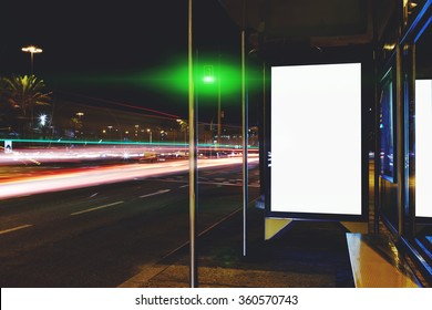 Blank electronic billboard with copy space for your text message or content, public information board on bus stop in the big city at night, advertising mock up with movement of cars on the background