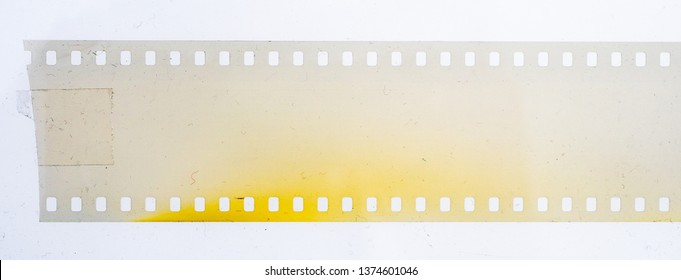 blank and empty 35mm vintage film strip on dusty background with tape