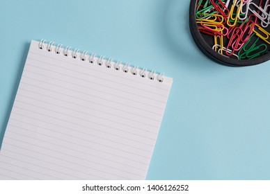 Blank empty notebook and clips placed above pastel colour table. Note paper plus stationary stick to modern background in tilted position. Artistic way of flat lays photography
