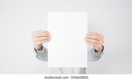 blank empty paper in man hand and wear shirt on white background.asian people