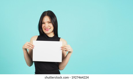Blank empty paper in teenage girl or woman's hand on green or Tiffany Blue background.she wear black dress