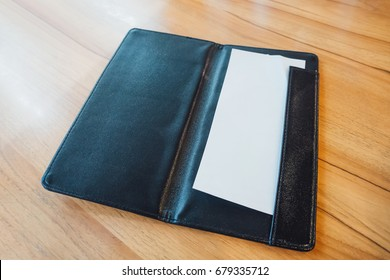 Blank empty white paper in black leather restaurant payment billing receipt folder on wood table