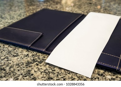 Blank empty white paper in restaurant payment billing receipt folder on granite table
