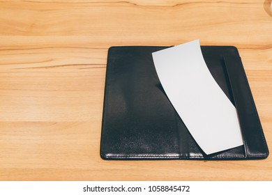 Blank empty white paper in restaurant payment billing receipt folder on wood table