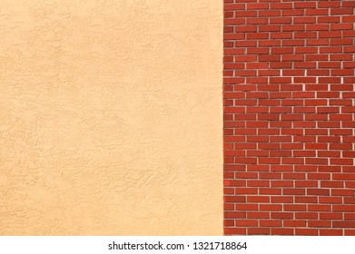 A blank empty yellow stucco wall joins to a red brick wall, outside.