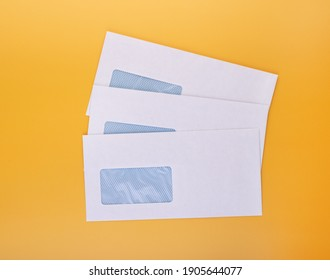 Blank envelopes with address window on yellow background. White paper envelopes mockup for business correspondence, postal stationery and corporate lettering - Shutterstock ID 1905644077