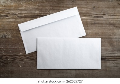 Blank envelopes on a dark wooden background. Back and front. Top view. Template for branding identity.