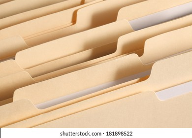 Blank file folder tabs in a filing cabinet drawer. Primary focus on tabs near the front of the image.