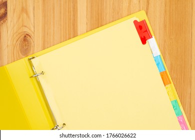 Blank file tabs in a yellow binder on wood desk mockup with copy space for your school or business message