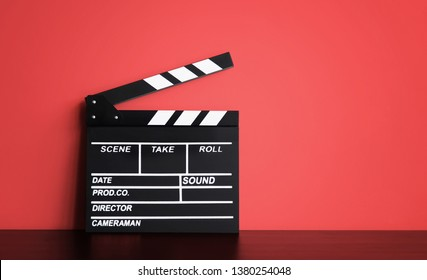 Blank Film clapper board or movie clapper cinema board , Slate film on black wooden with red wall background .cinema concept