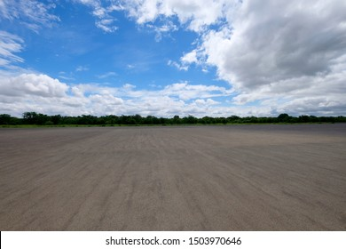blank flat asphalt ground. Green Trees on horizon. Sunny blue sky with magnificent white cloudscape. Wide angle
