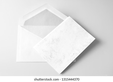 Blank folded greeting card and envelope over grey background