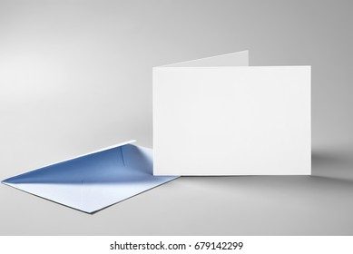 Blank folded standing card and envelope over grey background