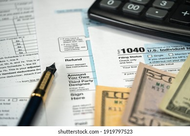Blank Form 1040 U.S. Individual Income Tax Return with Pen and banknotes. Tax Payment Concept. Filing Taxes Document. Selective focus