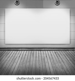 blank frame on white wall with spot light and wood floor in room for information message promotion at walkway.