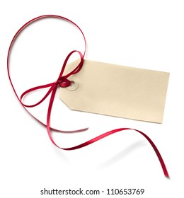 Blank gift tag with a red ribbon bow, isolated on white.