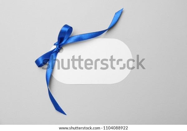 Blank gift tag with satin ribbon on light background, top view
