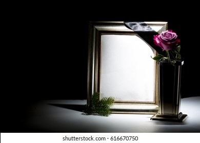 blank gilded mourning frame with bronze vase, pink rose,  and black tape on dark background