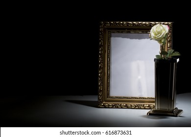 blank gilded mourning frame with bronze vase, white rose,  and black tape on dark background