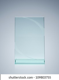 Blank glass award over gray background with copy space