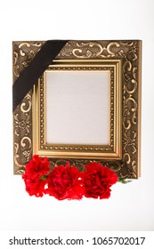 Blank gold mourning frame, with red carnations flower on bright background for condolence card