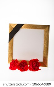 Blank gold mourning frame, with red carnation flowers on bright background for condolence card