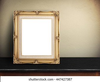 Blank Gold victorian picture frame on black marble table at yellow concrete wall,Template mock up for adding your design and leave space beside frame for adding more text.