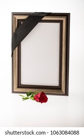 blank golden mourning frame with red rose on bright background for sympathy card