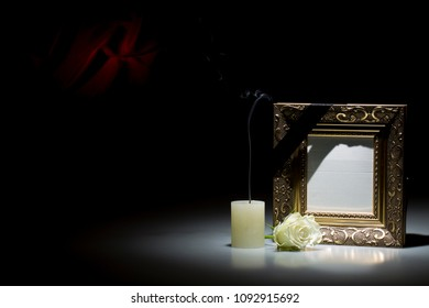 Blank golden mourning frame, with smoky candle and white rose, on dark background with red decoration