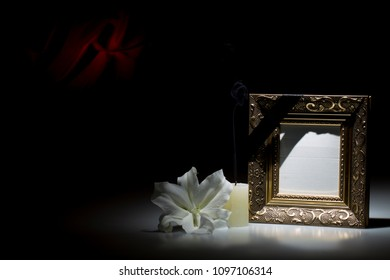 Blank golden mourning frame, with smoky candle and white lily flower on dark background with red decoration