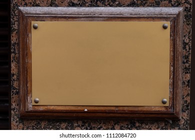 Blank golden plaque on a worn wooden frame attached to a marble wall column.