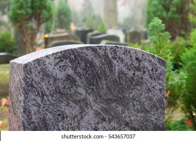Blank granite tombstone without inscription; other tombstones in the background