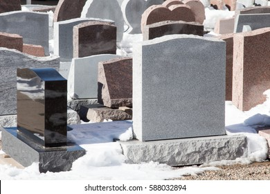 Blank grave stones crowded together in the snow