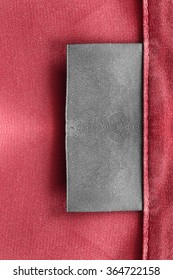 Blank gray clothes label on red satin