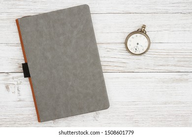 Blank gray journal with pocket watch on a weathered whitewash wood background with copy space for your message