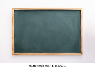 blank green chalkboard on a white wall, school and teaching concept, copy space for text