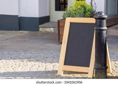 Blank green mockup of street wooden vintage signboard in front of the cafe.