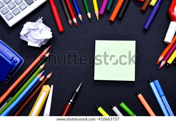 Blank green pink post-it note on blackboard surrounded by stationery.