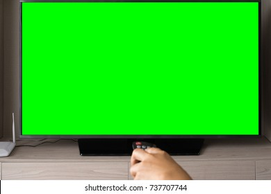 Blank green screen TV with defocused female hand holding remote control.