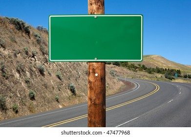 Blank green traffic sign on wooden electric pole against winding road