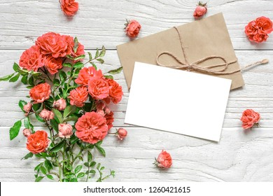 blank greeting card with bouquet of rose flowers in Living Coral color. Pantone color of the year 2019. Nature concept. Flat lay. mock up. top view with copy space