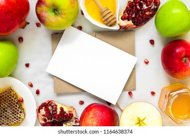 blank greeting card in frame made of honey, apple and pomegranate. traditional food for Jewish New Year Holiday, Rosh Hashanah. top view with copy space. mock up
