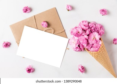 blank greeting card and ice cream cone of pink blossom cherry flowers in waffle cone on white marble background. flat lay. mock up. top view. wedding or holiday background