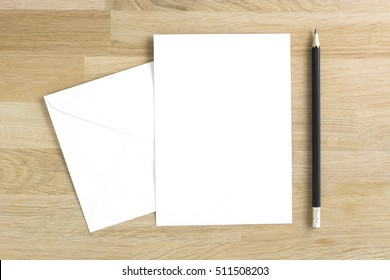 Blank greeting card mockup with pencil on wooden table