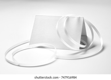Blank greeting card with ribbon over grey background