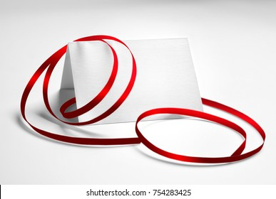Blank greeting or thank you card decorated with red ribbon