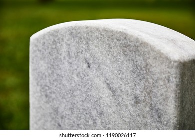A blank headstone in a cemetery with shallow depth of field