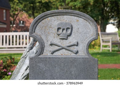 Blank headstone decorated with skull and crossbones