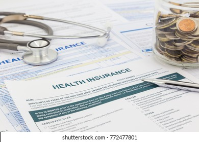 Blank health insurance forms with clinical stethoscope, silver pen and money world coins in glass container. Saving money for planing medical insurance budget.