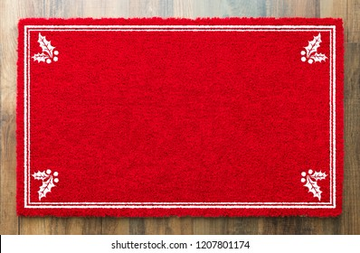 Blank Holiday Red Welcome Mat With Holly Corners On Wood Floor Background.